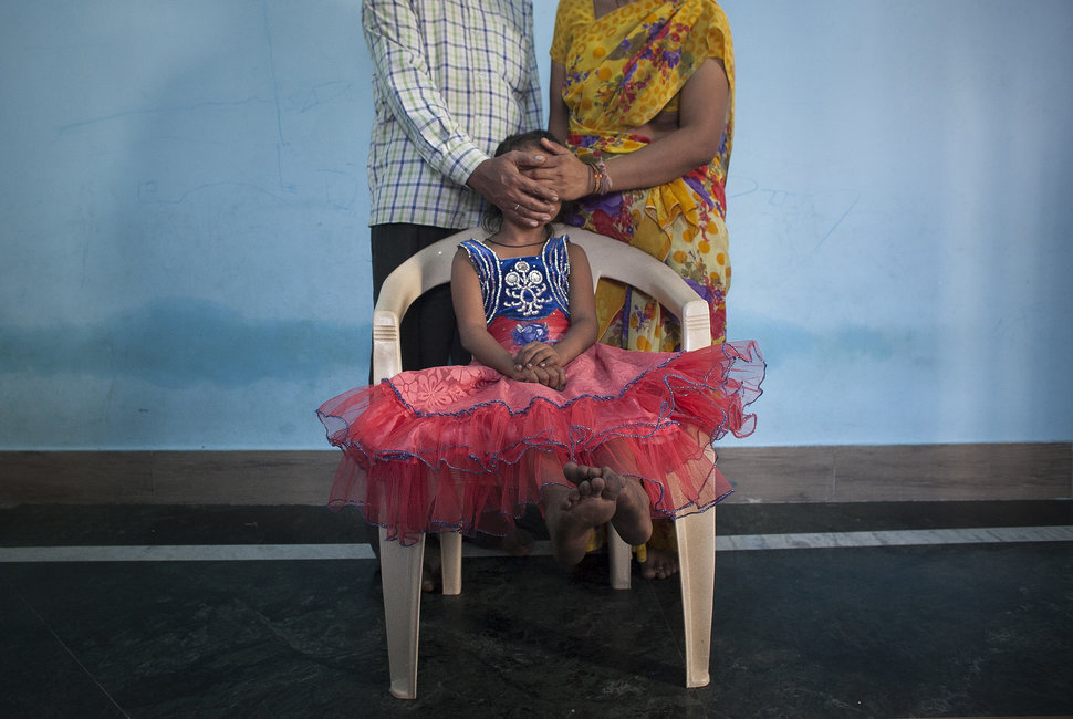 "MAHARASHTRA, INDIA - NOVEMBER 12: 5 year old Nirmala (name changed), who was raped by her mother's boss, poses for a photo with her mother and father on November 12, 2015 in Maharashtra, India. One day Nirmala's mother gave her money to go to the corner store and buy food. While Nirmala was walking the man came up to her and offered to buy her candy. He took her to a wooded area behind an apartment building complex, raped her, and inserted a pen inside her. He left her naked and bleeding heavily. She required two surgeries and stayed in the hospital for three months. They caught the man two weeks later. Since he's been in jail, his family keeps coming to Nirmala's family offering them money to drop the court case. Nirmala's family has since moved to a different neighborhood because the neighbors were gossiping, saying things like ""The girl's life is spoiled, what will you do now?"". Nirmala's mother says they won't accept the money offered by the rapist's family, that they want justice instead. (Photo by Getty Images)"